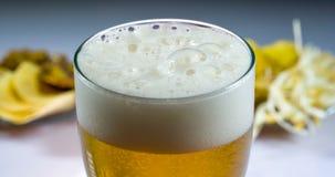 Vidrio de cerveza fría y de bocados almacen de metraje de vídeo