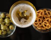Vidrio de cerveza ligera en fondo reflexivo negro Foto de archivo
