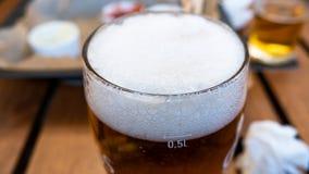Vidrio de cerveza ligera en un fondo del pub Cierre para arriba imagenes de archivo