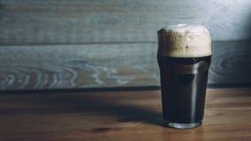 Vidrio de cerveza oscura en superficie de madera fotos de archivo