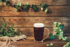 Vidrio de cerveza oscuro de cerveza dorada, cerveza inglesa marrón en la tabla de madera en barra o pub Fotografía de archivo