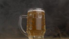 Vidrio de cerveza torcido en qué cerveza fresca se vierte en una neblina, primer, fondo negro, cámara lenta almacen de metraje de vídeo