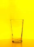 Vidrio de cerveza vacío sobre fondo amarillo Foto de archivo
