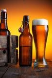 Vidrio de cerveza y cajón de la cerveza con las botellas Foto de archivo libre de regalías