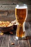 Vidrio de cerveza y de bocados Buena combinación de bebida malteada con las galletas y las nueces Imágenes de archivo libres de regalías