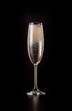 Vidrio de champán chispeante en fondo negro Imagenes de archivo