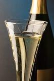 Vidrio de Champán con la botella del champán Foto de archivo