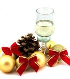 Vidrio de champán con las decoraciones de la Navidad en un fondo blanco Imagen de archivo libre de regalías