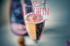 Vidrio de Champán con champán y la inscripción nobles en rosa en el alemán Gutschein, en cupón inglesa, vale, carte cadeaux Fotografía de archivo