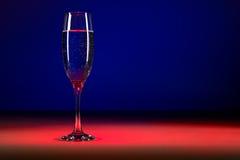 Vidrio de champán en fondo colorido Estudio tirado del vidrio de burbujeante Imagen de archivo