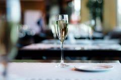 Vidrio de champán en la tabla Fotos de archivo libres de regalías
