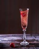 Vidrio de champán rosado en una tabla de madera Fresas en gla Imagen de archivo libre de regalías