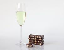 Vidrio de champán y de chocolate con las avellanas Fotos de archivo