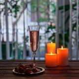 Vidrio de champán y de fresas rosados en una tabla de madera Imagen de archivo