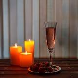 Vidrio de champán y de fresas rosados en una tabla de madera Foto de archivo libre de regalías