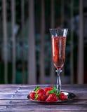 Vidrio de champán y de fresas rosados en una tabla de madera Fotos de archivo libres de regalías