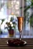Vidrio de champán y de fresas rosados en una tabla de madera Imagen de archivo libre de regalías