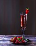 Vidrio de champán y de fresas rosados en una tabla de madera Fotos de archivo