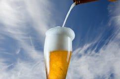 Vidrio de colada de cerveza de la botella fotografía de archivo