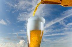 Vidrio de colada de cerveza de la botella imagen de archivo