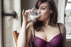 Vidrio de consumición hermoso de la mujer joven de leche Imagenes de archivo