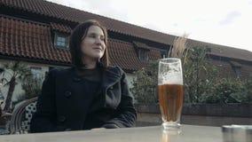 Vidrio de consumición de la mujer joven de cerveza en un restaurante de la calle La muchacha goza de la cerveza en un café en la  almacen de metraje de vídeo