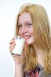 Vidrio de consumición rubio de la muchacha de leche Foto de archivo