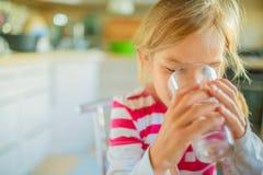 Vidrio de consumición sonriente de la niña de agua Imágenes de archivo libres de regalías