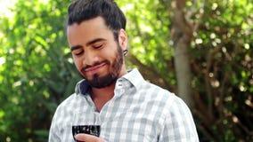 Vidrio de consumición sonriente del hombre de vino rojo almacen de metraje de vídeo