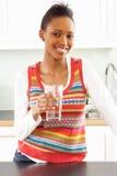 Vidrio de consumición de la mujer joven de agua en cocina Fotos de archivo