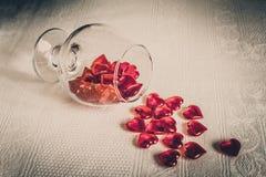 Vidrio de corazones rojos en un fondo blanco Fotografía de archivo