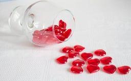 Vidrio de corazones rojos en un fondo blanco Fotos de archivo libres de regalías