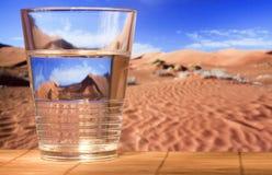 Vidrio de cristal con agua en desierto Foto de archivo libre de regalías