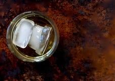 Vidrio de escocés con tres cubos de hielo, dejado de centro, en un fondo marrón fotografía de archivo