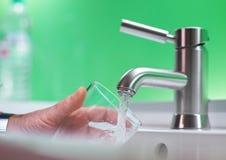 Vidrio de Fillig de agua de distribución, agua potable Fotos de archivo