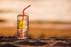 Vidrio de Gin Tonic con la rebanada de la paja y de la cal en la playa, en la puesta del sol Long Beach, Ko Lanta, Tailandia fotografía de archivo libre de regalías