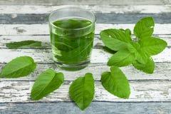 Vidrio de hojas del té de la menta y de menta en la tabla imágenes de archivo libres de regalías