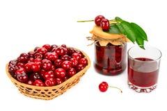 Vidrio de jugo, cesta de cerezas y tarro de atasco foto de archivo libre de regalías