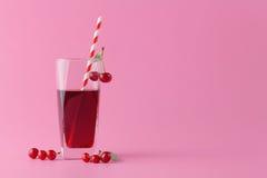 Vidrio de jugo fresco con las cerezas en fondo brillante Imágenes de archivo libres de regalías