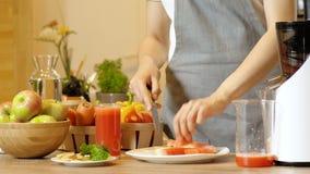 Vidrio de jugo fresco de la sandía en la tabla en cocina Mujer joven que corta una sandía madura en fondo almacen de video