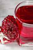 Vidrio de jugo de la granada con la fruta fresca de la granada Imagenes de archivo
