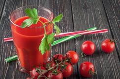 Vidrio de jugo de tomate en la tabla de madera Fotos de archivo libres de regalías