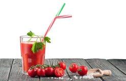 Vidrio de jugo de tomate en una tabla de madera Imagen de archivo