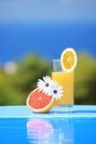 Vidrio de jugo y de flores en una piscina fotos de archivo libres de regalías