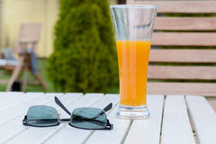 Vidrio de jugo y de gafas de sol en la tabla Imagen de archivo