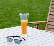 Vidrio de jugo y de gafas de sol en la tabla Imagen de archivo libre de regalías