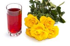 Vidrio de jugo y de rosas amarillas en un fondo blanco Imagen de archivo