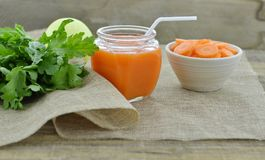 Vidrio de jugo de zanahoria con la zanahoria de las rebanadas en el cuenco blanco Fotos de archivo