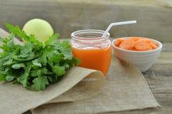 Vidrio de jugo de zanahoria con las rebanadas en el cuenco blanco en de madera Imagenes de archivo