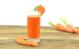 Vidrio de jugo de zanahorias y de zanahorias frescas de las rebanadas en de madera Fotografía de archivo